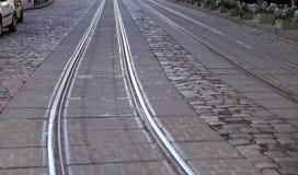 Hintergrund Bild einer alten Straße mit der grauen Steinpflasterung der Straßen- und Metallschienen stockfotos