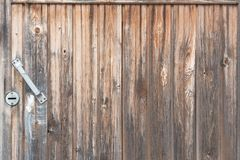 Hintergrund in der Art ein rustikales von den alten vertikalen hölzernen unbemalten Brettern mit dem Griff Stockfotos