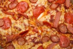 Hintergrund der Nahaufnahmepizza mit Belag von Schinken, von Würsten und von Käse Stockfoto