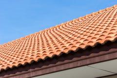 Hintergrund des Dachs der roten Fliesen und des blauen Himmels stockfotografie