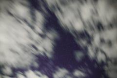 Hintergrund des dunkelblauen nächtlichen Himmels mit unzähligen Funkelnsternen und bewegenden weißen Wolken auf auf ihm Lizenzfreies Stockbild