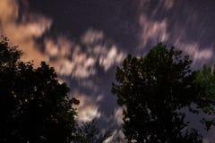 Hintergrund des dunkelblauen nächtlichen Himmels mit unzähligen Funkelnsternen und bewegenden weißen Wolken auf auf ihm Stockfoto