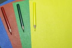 Hintergrund des farbigen Papiers und der farbigen Bleistifte Lizenzfreies Stockbild