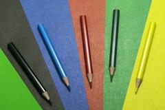 Hintergrund des farbigen Papiers und der farbigen Bleistifte Lizenzfreie Stockfotografie