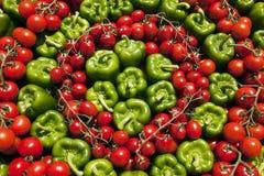 Hintergrund des grünen grünen Pfeffers und der roten Tomaten Stockfotografie