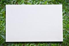 Hintergrund des grünen Grases mit Weißbuch Lizenzfreie Stockfotografie