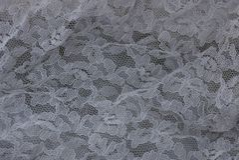 Hintergrund des grauen Weiß eines Stückes des Stoffvorhangs Stockbilder