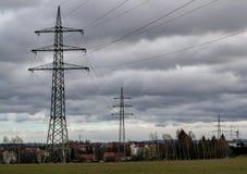 Hintergrund des großen elektrischen Hochspannungspfostens, der zur Stadt überschreitet stockfoto