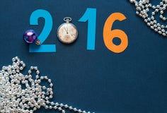 Hintergrund des neuen Jahres mit Datum 2016, Uhren und Festivalperlen Lizenzfreie Stockfotos