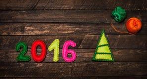 Hintergrund 2016 des neuen Jahres mit dem Weihnachtsspielzeug hergestellt vom Filz auf dunklem Rost Stockfotos