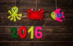 Hintergrund 2016 des neuen Jahres mit den Weihnachtshandgemachten Spielwaren an hergestellt vom Filz Lizenzfreie Stockbilder