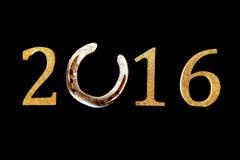 Hintergrund des neuen Jahres 2016 mit einem Hufeisen Stockfotografie