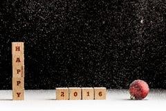 Hintergrund 2016 des neuen Jahres mit fallendem Schnee und einem roten Weihnachten b Stockfotos