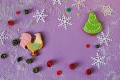 Hintergrund des neuen Jahres mit Lebkuchenhahn, -schneeflocken und -tanne Stockfotos