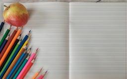Hintergrund des offenen Schulnotizbuches, der farbigen Bleistifte und des Apples Stockfoto