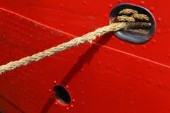 Hintergrund des roten Lieferungsrumpfs mit Seil Stockfoto