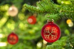 Hintergrund des roten Weihnachtsballs auf Tannenbaum lizenzfreie stockbilder