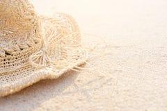 Hintergrund des Sandstrandes mit Zusatzstrohhut in der Sommerzeit Kann Text nach links hinzuf?gen stockbild