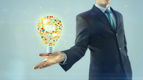 Hintergrund des weißen Lichtes der Geschäftsmann-Geschäftsmanninspirationsideenkonzeptgriffartdesign-Lampenbirne an Hand stock abbildung