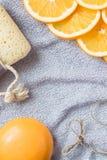 Hintergrund für das Baden des Themas: die orange Seife, die Scheiben der Orange und der Badeschwamm auf dem Tuch Stockfotografie
