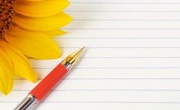 Hintergrund für Text mit einer Sonnenblume und einem Stift Lizenzfreie Stockfotografie