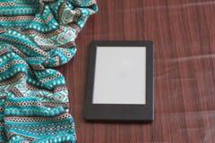 Hintergrund gebunden mit blauer Strickjacke, Holztisch und Tablette Lizenzfreie Stockfotos