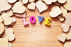 Hintergrund geschaffen vom braunen Herzen und von den Buchstaben auf dem Brett Stockbilder