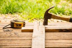 Hintergrund-Handwerkerwerkzeug mit altem Hammer mit Maßband und kleine Nägel auf hölzernem Hintergrund und Ansicht im Freien Lizenzfreie Stockbilder