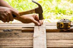 Hintergrund-Handwerkerwerkzeug mit altem Hammer mit Maßband und kleiner Ansicht der Nägel und des Arbeitens im Freien Hintergrund Stockbild