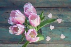 Hintergrund mit Blumenstrauß von rosa Tulpen und von Herzen auf blauem Schmutz Stockfotografie