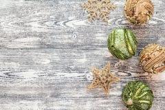 Hintergrund mit den goldenen und grünen Weihnachtsdekorationen auf grauem w Stockbilder