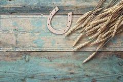 Hintergrund mit den Ohren des Weizens und des dekorativen Hufeisens auf alter Querstation Lizenzfreie Stockfotos