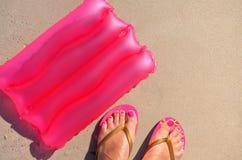 Hintergrund mit einem aufblasbaren Kissen und Füße in Klapse auf dem Sand lizenzfreies stockfoto