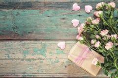 Hintergrund mit einem Blumenstrauß von rosa Rosen und von Geschenkbox auf alter Querstation Stockbild