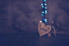 Hintergrund mit einem hölzernen Herz und Schmetterlinge bokeh Im Herzen der Wortliebe Lizenzfreies Stockbild
