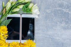 Hintergrund mit einem Platz für eine Aufschrift sind Smartphones, eins von ihnen mit einem defekten Schirm und um Blumen Lizenzfreie Stockfotos
