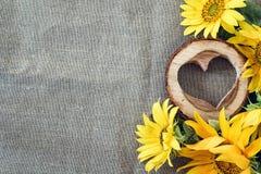 Hintergrund mit gelben Sonnenblumen und hölzernem Herzen auf dem Segeltuch Stockfotos