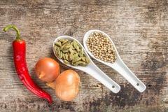 Hintergrund mit Gewürzen und Gemüse auf Planke Lizenzfreies Stockfoto