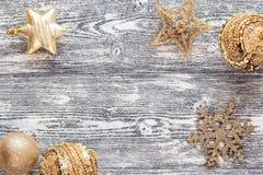 Hintergrund mit goldenen Weihnachtsdekorationen auf grauem hölzernem Eber Stockfotografie