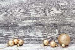 Hintergrund mit goldenen Weihnachtsdekorationsbällen auf grauem woode Lizenzfreie Stockfotografie