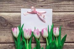Hintergrund mit leerer Karte und rosa Tulpen auf hölzernem Eber des Schmutzes Lizenzfreie Stockbilder