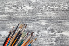 Hintergrund mit Malerpinseln auf Weiß malte hölzerne Bretter Winkel des Leistungshebels Lizenzfreies Stockfoto
