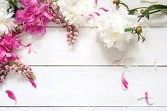 Hintergrund mit Pions und und Lupines auf weißem Holztisch Winkel des Leistungshebels Lizenzfreies Stockbild