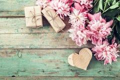 Hintergrund mit rosa Pfingstrosen, Geschenkbox und einem hölzernen Herzen auf altem Stockfotos
