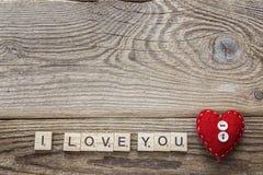 Hintergrund mit rotem Herzen und eine Liebeserklärung auf altem Brett Stockfoto