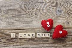 Hintergrund mit rotem Herzen und eine Liebeserklärung auf altem Brett Lizenzfreies Stockfoto