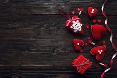 Hintergrund mit roten Herzen und Geschenkbox auf altem dunklem Holztisch Lizenzfreie Stockfotografie