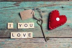 Hintergrund mit roten Herzen und Weinleseschlüssel auf alten Brettern Lizenzfreie Stockfotos