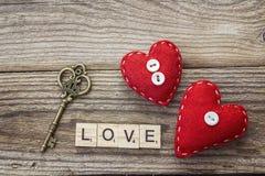 Hintergrund mit roten Herzen und Weinleseschlüssel auf alten Brettern Lizenzfreies Stockbild