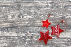 Hintergrund mit roten Weihnachtsdekorationen spielt auf grauem hölzernem b die Hauptrolle Stockfotografie